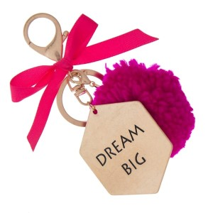 """Gold tone key chain or bag charm stamped with """"Dream Big"""" and a fuchsia pom pom. Approximately 5.5"""" in length."""