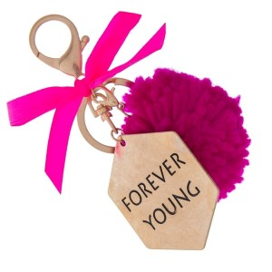"""Gold tone key chain or bag charm stamped with """"Forever Young"""" and a fuchsia pom pom. Approximately 5.5"""" in length."""