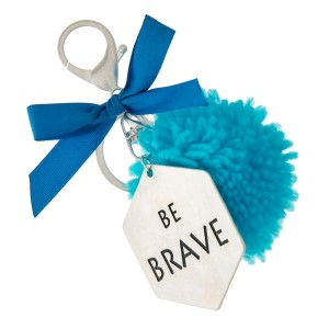 """Silver tone key chain or bag charm stamped with """"Be Brave"""" and a blue pom pom. Approximately 5.5"""" in length."""