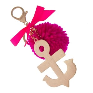 """Gold tone key chain or bag charm stamped with an anchor pendant and a fuchsia pom pom. Approximately 5.5"""" in length."""