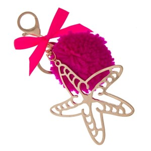 """Gold tone key chain or bag charm stamped with a starfish pendant and a fuchsia pom pom. Approximately 5.5"""" in length."""