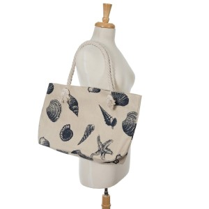 """Canvas tote bag with a top zipper and a seashell print. 45% polyester and 55% cotton. Measures 20"""" x 12"""" in size with a 10"""" handle drop."""