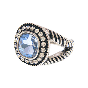 Varnished silver tone stretch ring featuring a light blue crystal rhinestone center surrounded by crystal clear rhinestones.