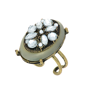 Burnished gold tone adjustable ring featuring an ivory stone with crystal clear rhinestone decor.