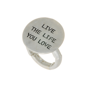 "Worn silver tone stretch ring featuring a disk stamped ""LIVE THE LIFE YOU LOVE""."