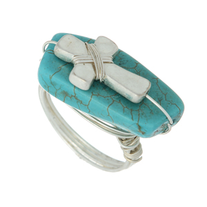 Silver tone wire wrapped ring featuring a turquoise stone with a cross focal. Size 8 only.