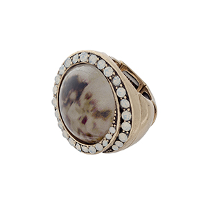 Burnished gold tone stretch ring with a brown stone focal surrounded by white opal rhinestones.