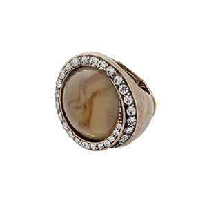 Burnished gold tone stretch ring with a tan stone focal surrounded by clear rhinestones.
