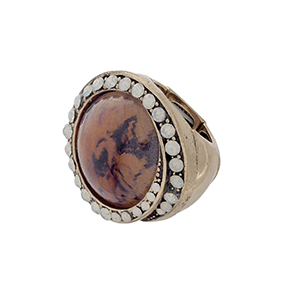 Burnished gold tone stretch ring with an orange stone focal surrounded by white opal rhinestones.
