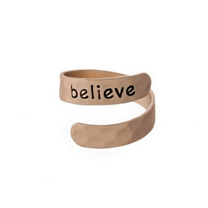 "Hammered copper tone, adjustable ring stamped with ""Believe."""