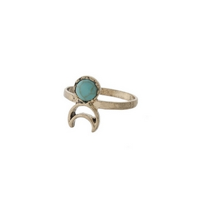 Gold tone ring with a turquoise stone and a cutout crescent. Approximately a size 7.