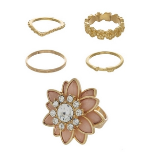 Gold tone five piece ring set featuring a pale pink stone flower ring and small knuckle rings. Assorted sizes from 4 to 7.